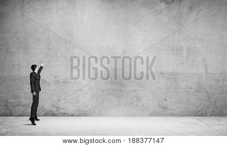 Businessman in empty concrete room drawing on wall