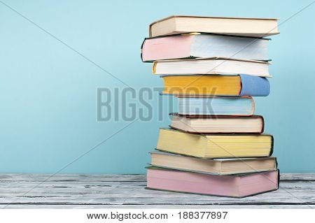 Book stacking. Open book, hardback books on wooden table and background. Back to school. Copy space for text