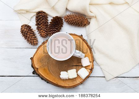 Cup with hot chocolate and marshmallows a row of cones and a knitted blanket on a white wooden background