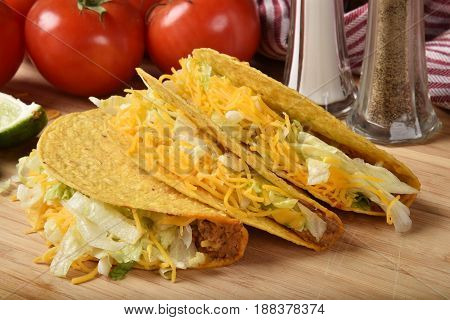 Homemade tacos on a cutting board with ripe tomatoes