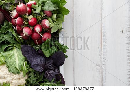 Fresh vegetables and herbs in wooden box on white table, top view