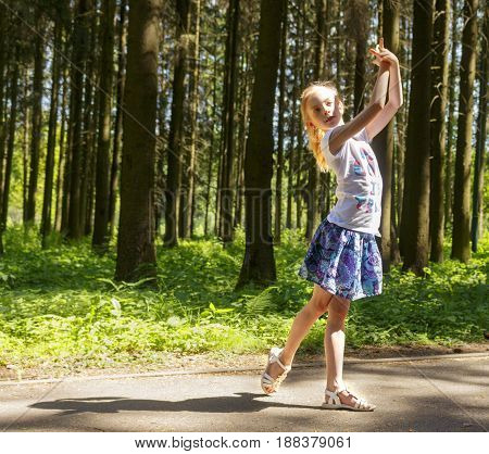 Young attractive girl is dancing in the park
