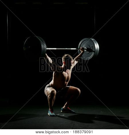 Fitness training. Man doing sit ups exercise with barbell in dark gym.