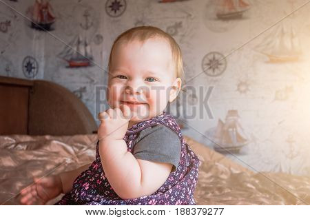 A One-year-old Baby Laughs Playfully And Holds His Hand To His Chin.