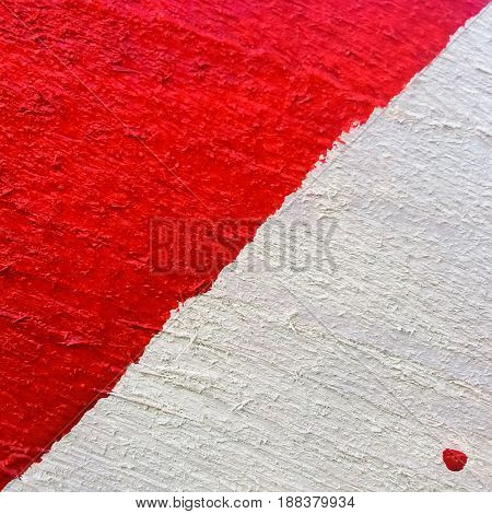 Background or texture of red-white painted rough wooden board close-up with diagonal line and drops paint