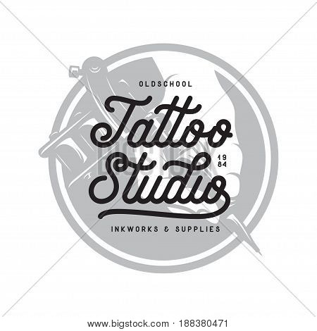Tattoo studio typography emblem. Hand holding tattoo machine. Vector vintage illustration.