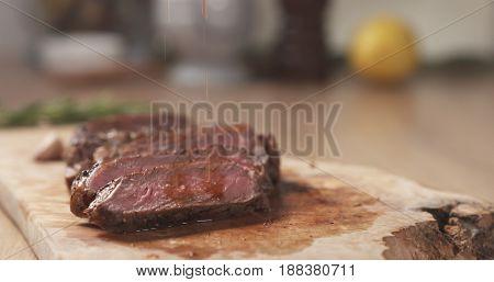 pouring meat juice on medium rib eye steak on board, wide photo