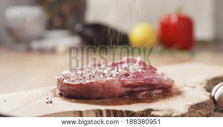 pepper falling on raw rib eye steak on board, wide photo