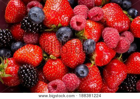 Mixed fresh soft berry fruits on plate