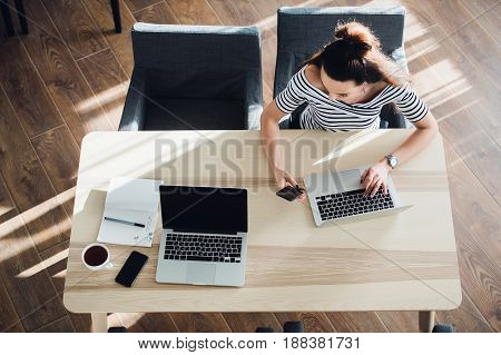 Busy young woman texting with mobile phone and writing notes while sitting at her desk. Pretty caucasian female working in home office or a cafe with her laptop