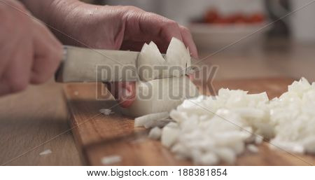 woman hands chopping white onion on cutting board, wide photo
