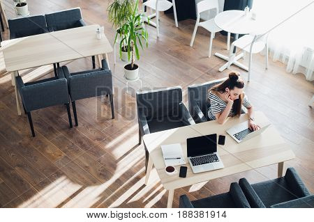 Young woman casually working on her laptop in a cafe. Bored attractive female sitting with a cup of coffee at work
