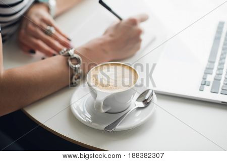 Hot art Latte Coffee in a cup on wooden table and Coffee shop blur background with woman's hands