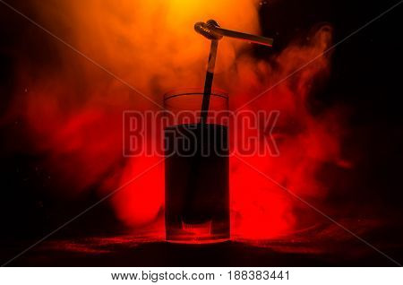 Glass Of Red Alcoholic Cocktail On Dark Background With Smoke And Backlight. Fire Hot Coctail. Club