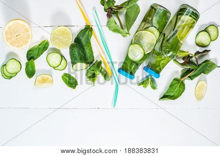 Cold and refreshing infused detox water with lime mint and cucumber in a bottle on white wood background. Copyspace and top view