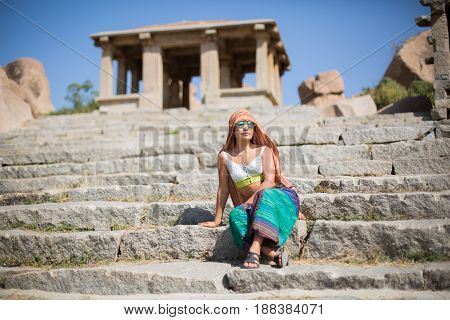 A girl in a cloak sits on stone steps at the foot of the temple