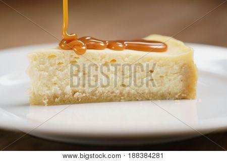 caramel sauce pour on cheesecake on plate closeup, shallow focus