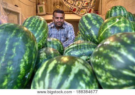Bandar Abbas Hormozgan Province Iran - 16 april 2017: Portrait of a seller in a huge pile of large watermelons.