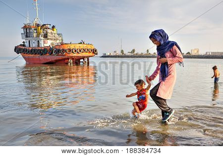 Bandar Abbas Hormozgan Iran - 16 april 2017: Young woman in hijab walking on water along surf line holding the hand of a little boy against background of an orange towboat standing on shallows.