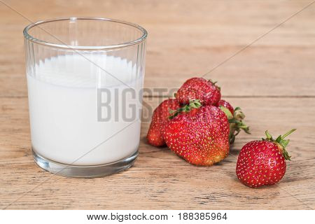 Ripe strawberry and a glass of milk on an old wooden table close-up