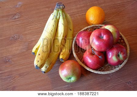 Fruit bananas apples orange on a wooden table background