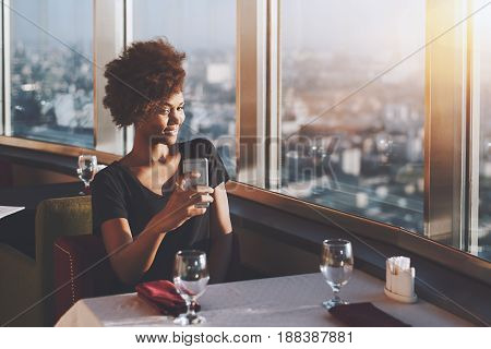 Naughty curly afro american girl is sitting in luxury cafe on the top of modern skyscraper and making selfie on frontal cam of her cell telephone with copy space for text logo or your advertising