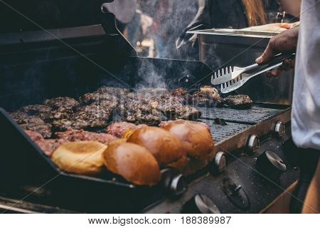 Cooking Delicious Juicy Meat Burgers And Buns On The Grill Outdoor.