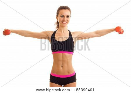 young beautiful girl smiling keeps hands at the sides with dumbbells and looking forward is isolated on a white background