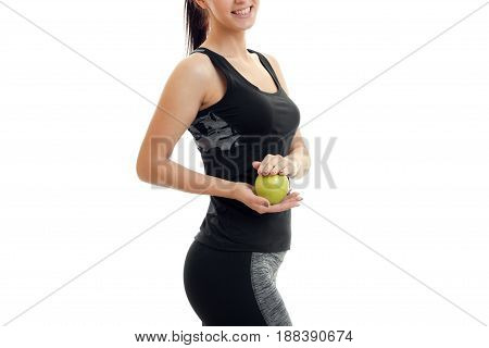 Slim young girl stands sideways and holding a Green Apple close-up isolated on white background