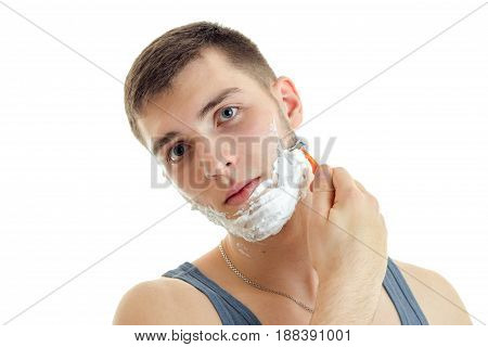 Portrait of a remarkable young man with foam on his face that tilted head and shaved closeup isolated on white background