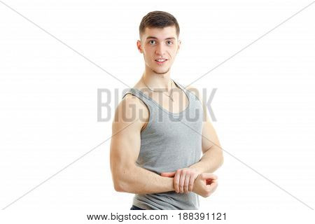 beautiful sporty guy stands in the grey t-shirt smiles and shows muscle on hand isolated on white background