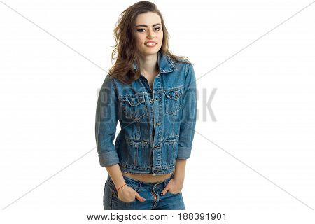 joyful young girl stands in jeans jacket is smiling looks straight and keeps hands in his pockets is isolated on a white background