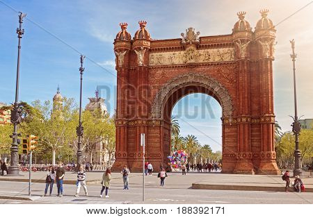 Baecelona Spain - 26 March 2017: People walking through the Arc de Triomf which is a triumphal arch in the city of Barcelona in Catalonia Spain. The arch is built in reddish brickwork in the Neo-Mudejar style