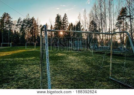 Abandoned frozen soccer field in a  sunset