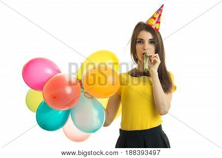 a wonderful sweet girl holding a lot of air of different balls looks ahead and blowing in the horns isolated on white background
