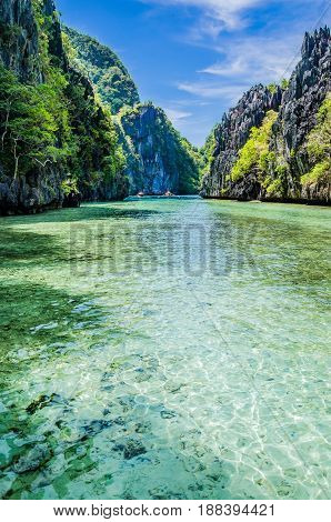 Tropical landscape with rock islands, lonely boat and crystal clear water, Palawan, Philippines.