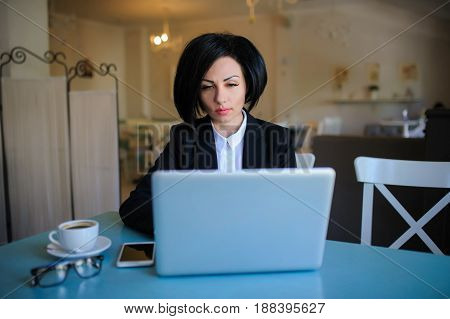 Business Lady Dressed In Black Suit Working On A Laptop