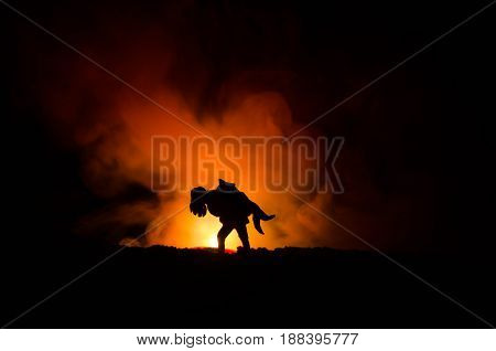 A Silhouette Of A Man Holding On To The Woman. Rescue Saviour Concept. Escape From Fire Or Danger. H