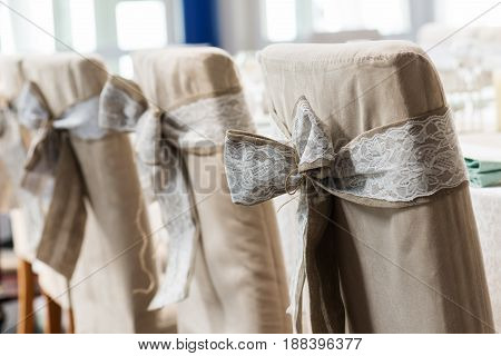 Festive wedding ceremony chairs decoration with bows of natural rustic style.