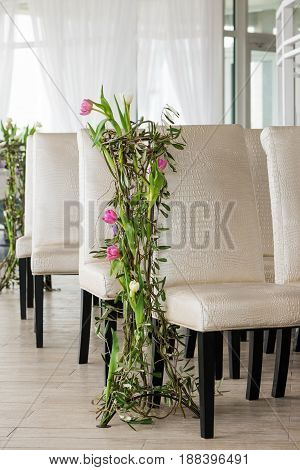 Floor composition with natural flowers near luxury chairs in hall for ceremonies and celebrations.