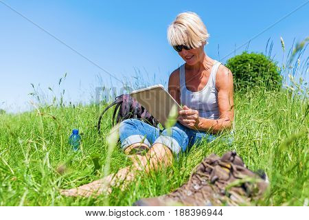 Mature Woman With Table Pc At A Hiking Rest