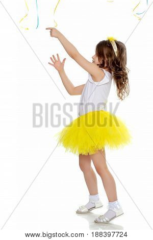 Pretty little blonde girl in a short bright yellow skirt and white blouse.Girl turned sideways to the camera and catches with hands in ropes from the balloons.Isolated on white background.