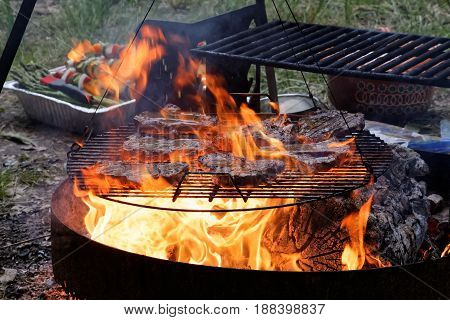 Beef steaks on an outdoor grill with flames and wood logs.