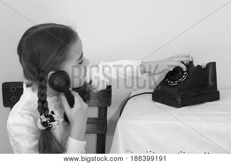 A beautiful little schoolgirl girl in a white blouse and black long skirt, with neatly braided pigtails on her head.She sits on an old Viennese chair and talks on an old telephone. Interior of the fifties of the last century.