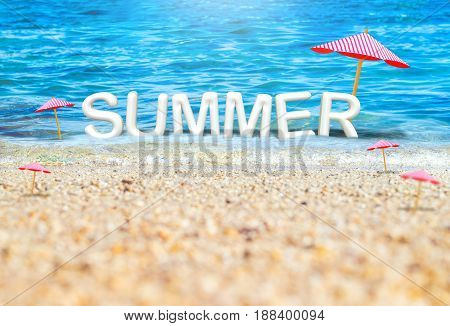Summer (3D Rendering text) white word with beach umbrella on sand beach and blue sea blur backgroundSummer Vacation concept.