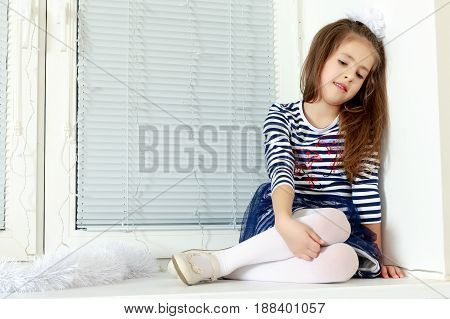 Little girl in blue striped dress and a white bow on her head.She sits at the window with sad eyes something lost in thought.