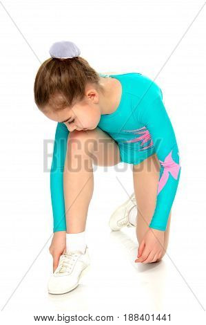 Very flexible little girl gymnast, junior school age, in a beautiful gymnastic swimsuit turquoise.She bent over to fix the shoes on her leg.Isolated on white background.