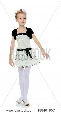 Beautiful little blonde girl dressed in a white short dress with black sleeves and a black belt.Girl poses for the camera.Isolated on white background.