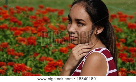 Teenage Girl And Shyness Sitting in Flower Meadow
