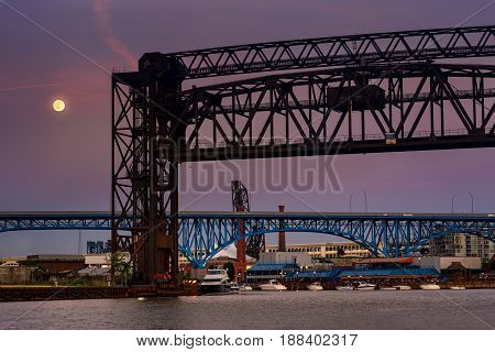 The full moon of summer rises above the bridges over the Cuyahoga in Cleveland Ohio